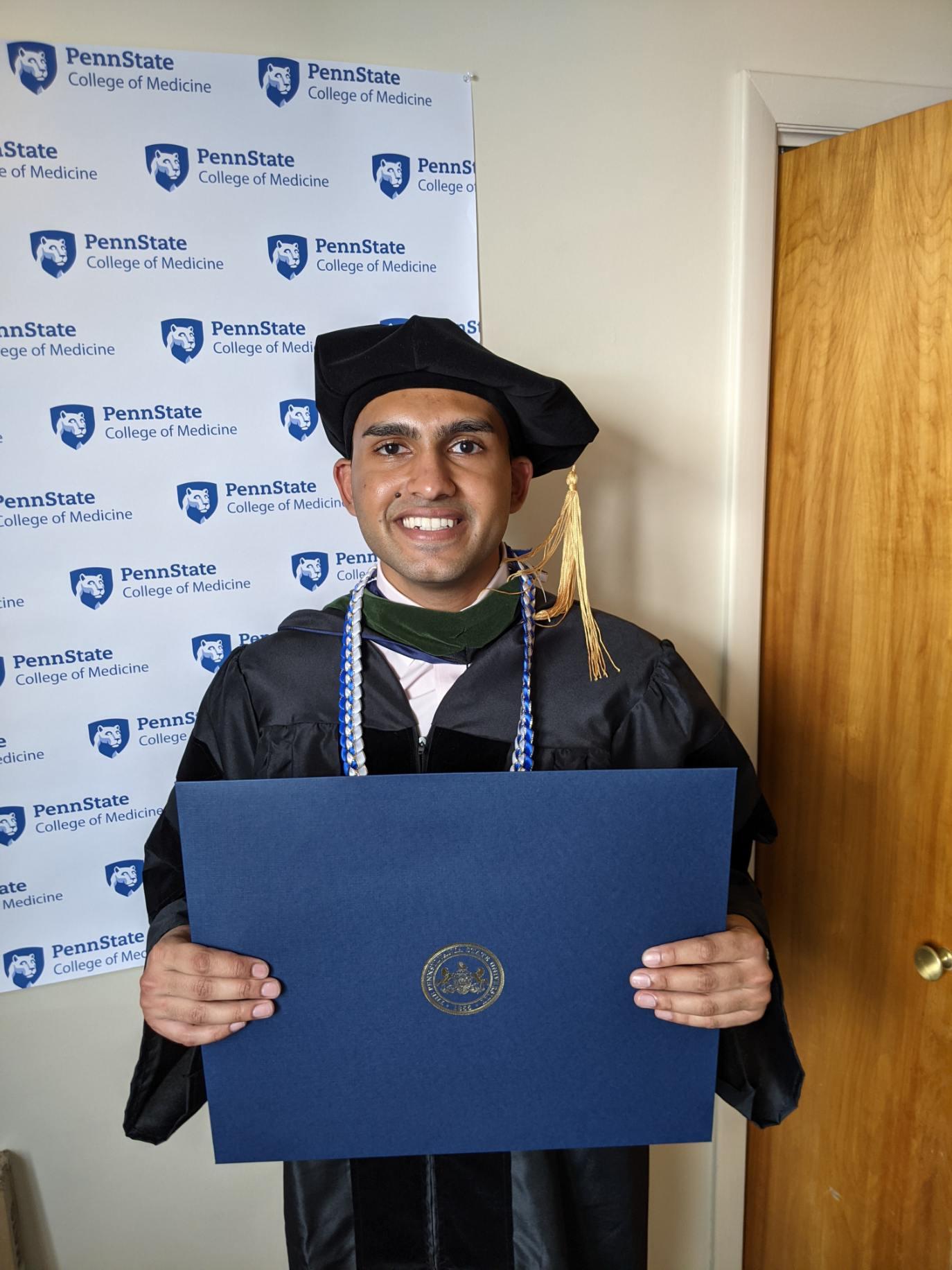 A man in graduation regalia holds a diploma.
