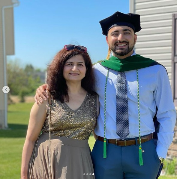 Anuj Mehta and a woman stand outdoors. He is wearing graduation regalia.