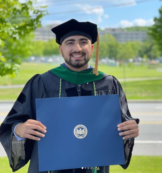 Anuj Mehta stands in front of Penn State Health Milton S. Hershey Medical Center holding a diploma and wearing graduation regalia.