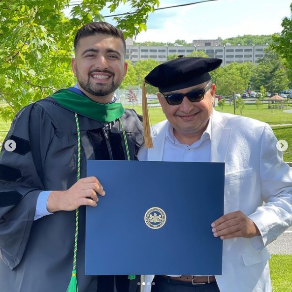 Anuj Mehta and an older man stand in front of Penn State Health Milton S. Hershey Medical Center holding a diploma. Mehta is wearing graduation regalia.