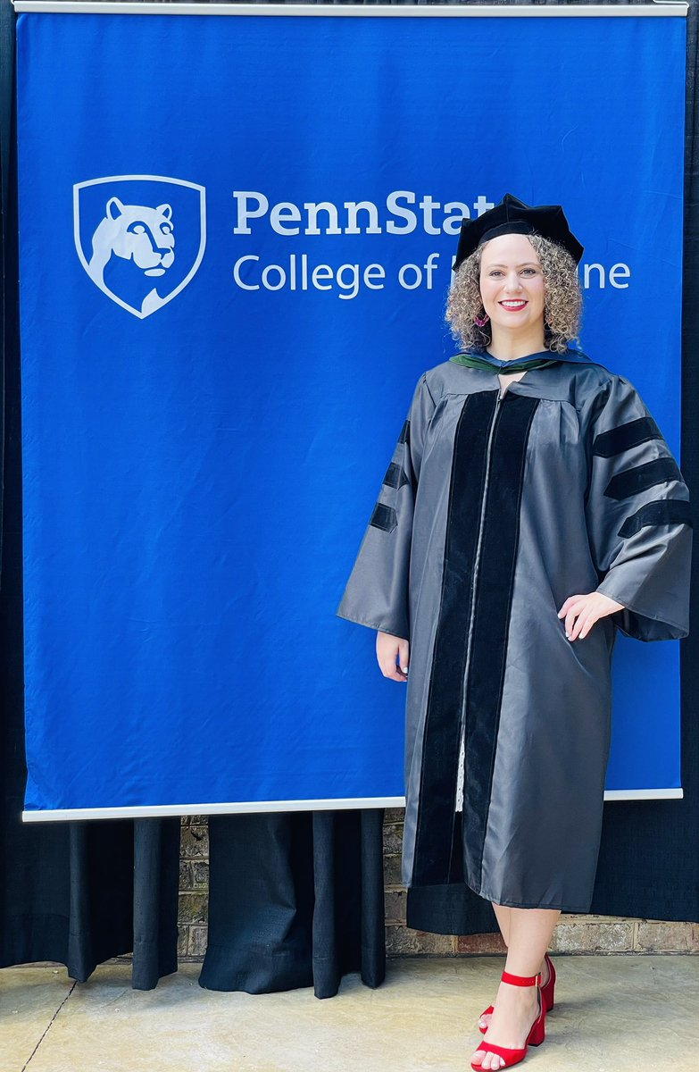 Sarah Erlikh stands in front of a Penn State College of Medicine banner wearing graduation regalia.