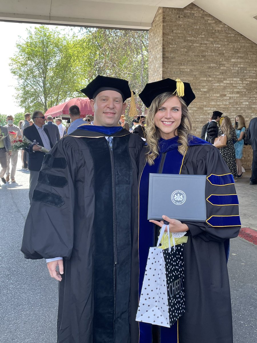 Yuval Silberman and Caitlin Coker stand outside Penn State College of Medicine wearing academic regalia.
