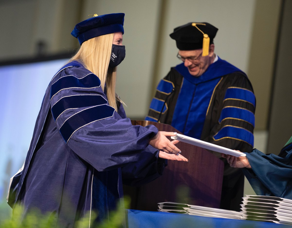 Erika Dahl is presented with her Penn State College of Medicine diploma by a man in graduation regalia.