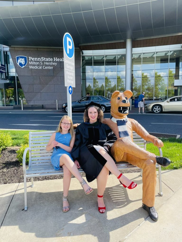 Sarah Erlikh sits on a bench at Penn State Health Milton S. Hershey Medical Center with a young girl.