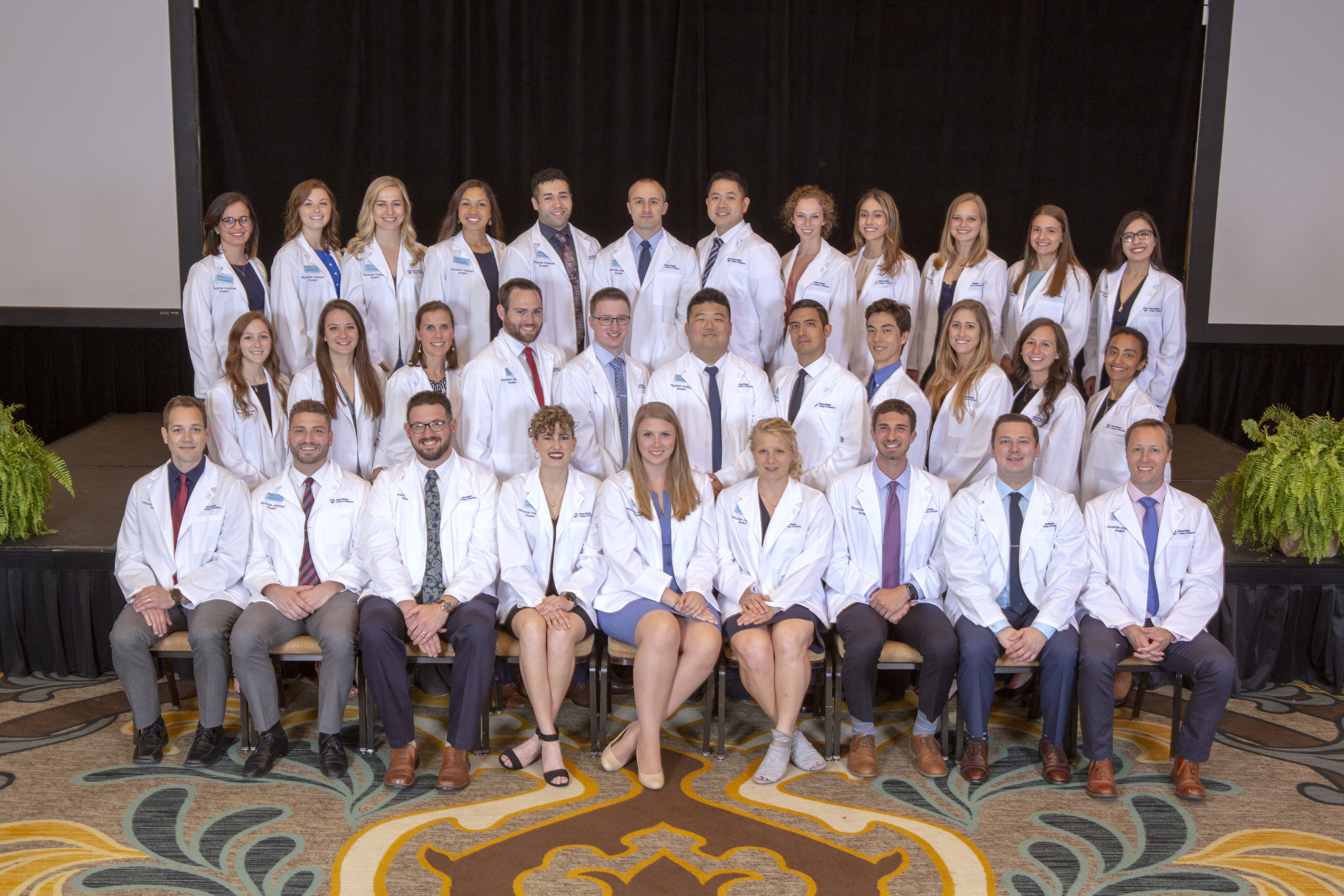 A large group of physician assistant students are pictured in three rows.