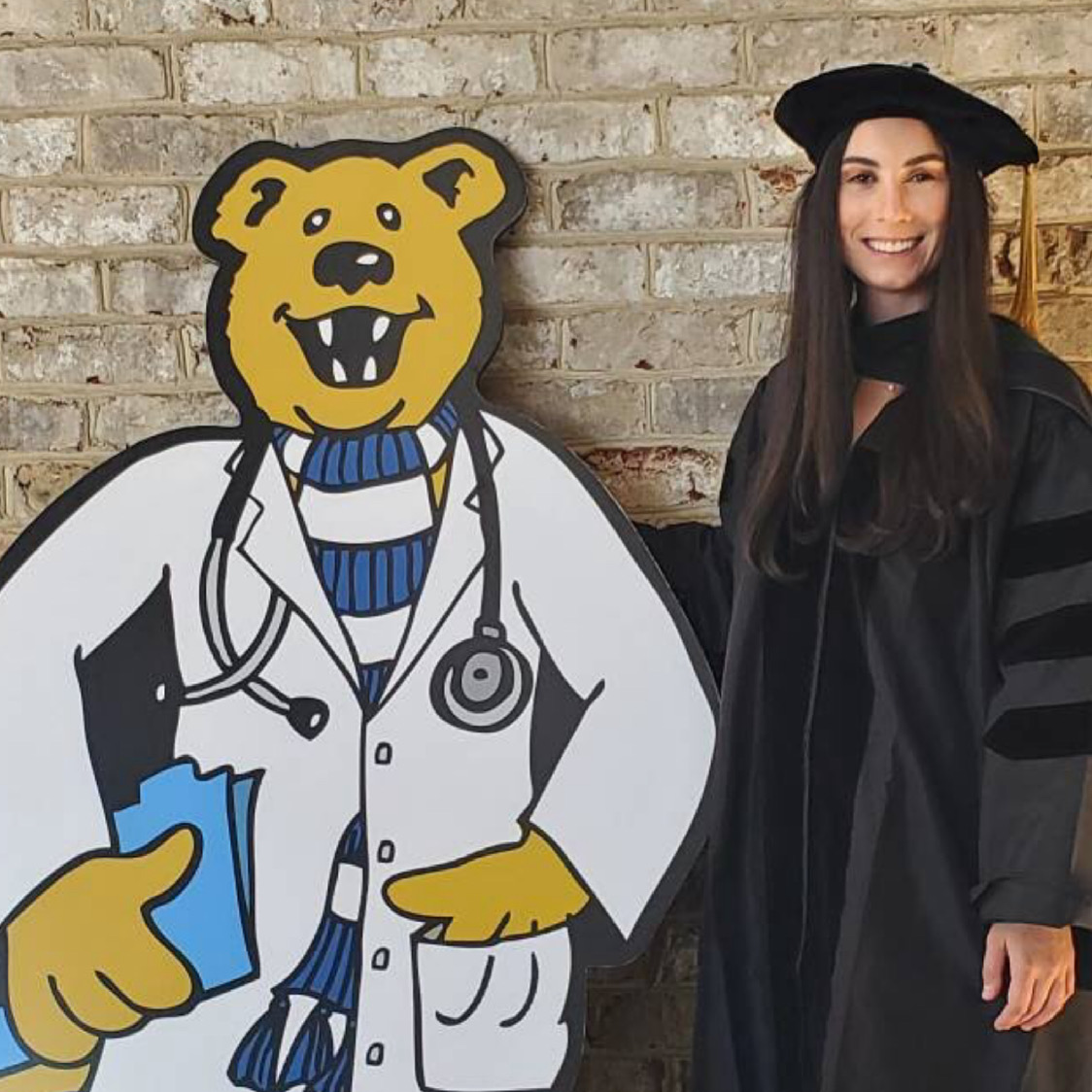 A woman in graduation regalia stands next to a large cutout of Penn State's Nittany Lion mascot.