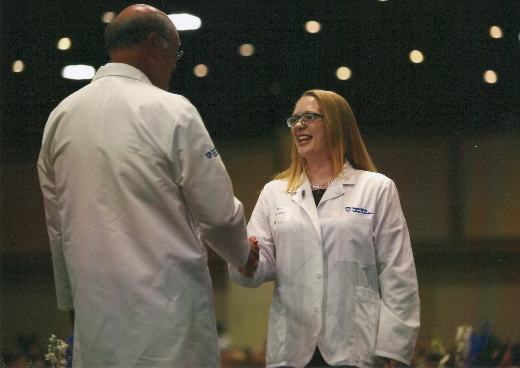 A woman wearing a white coat shakes the hand of a man on a stage.