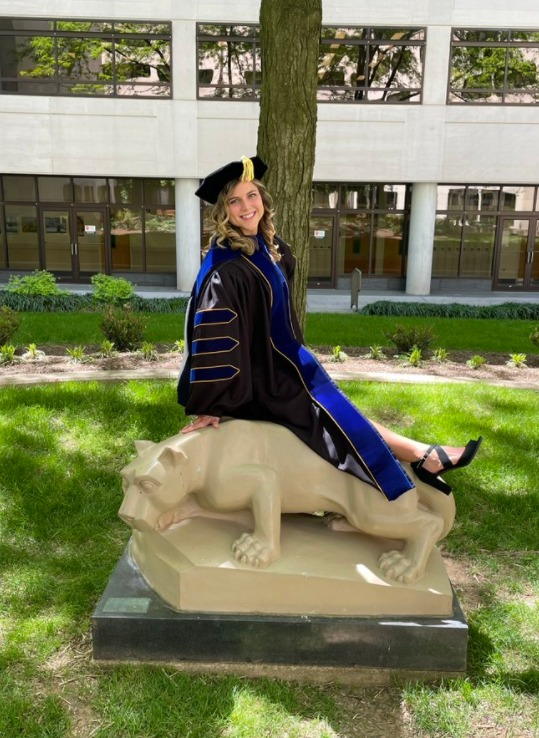 Caitlin Coker, MD, PhD, sits on the Penn State Nittany Lion statue in the courtyard of Penn State College of Medicine in May 2021. She is wearing graduation regalia.