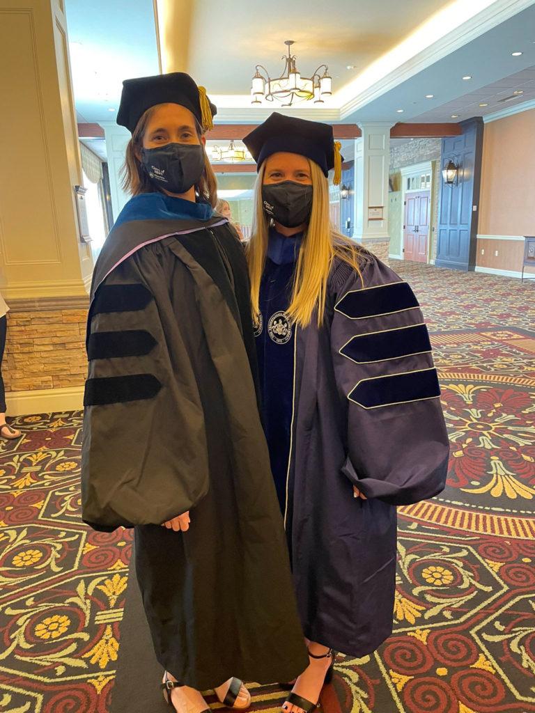 Dr. Katherine Aird and Dr. Erika Dahl wear graduation regalia and masks.