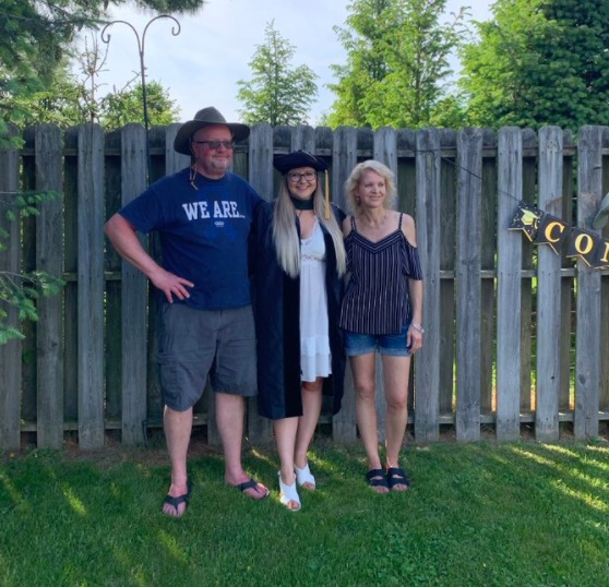Madison Goss stands with a man and woman near a fence with a Congratulations banner hanging on it. She is wearing graduation regalia.