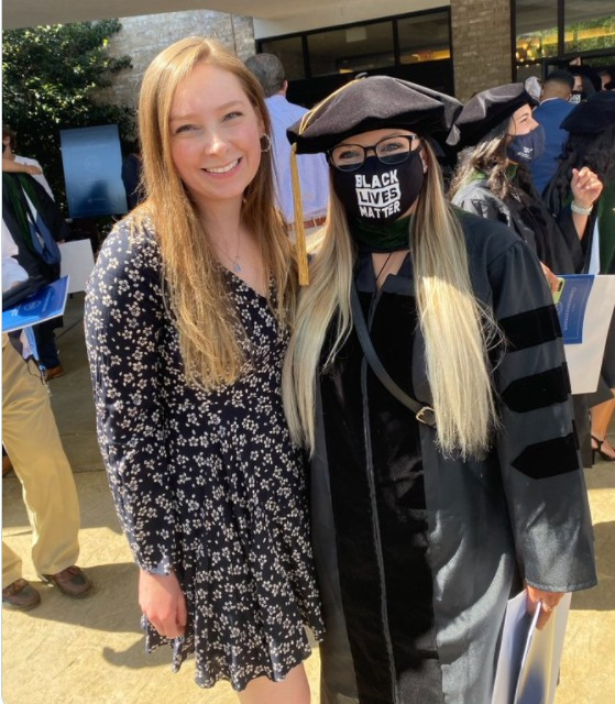 Madison Goss and another woman stand outdoors. Goss is wearing graduation regalia and a Black Lives Matter mask.