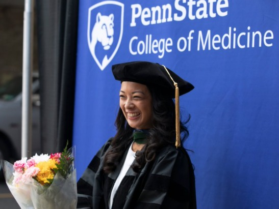 Nicole Rodis smiles while standing in front of a Penn State College of Medicine banner and holding flowers. She is wearing graduation regalia.