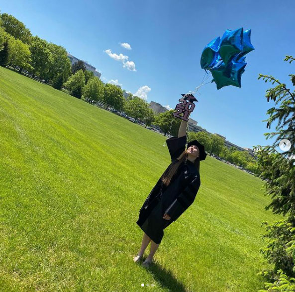 Paige Chardavoyne is holding balloons outside Penn State Health Milton S. Hershey Medical Center while wearing graduation regalia.