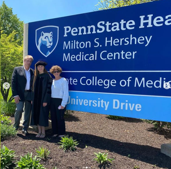 Paige Chardavoyne stands with 2 other people in front of the sign at Penn State Health Milton S. Hershey Medical Center and Penn State College of Medicine.