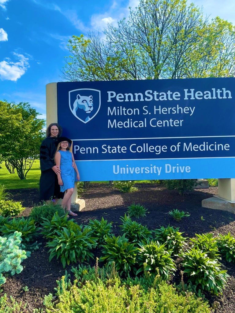 Sarah Erlikh stands next to the Penn State Health Milton S. Hershey Medical Center and Penn State College of Medicine sign with a young girl.