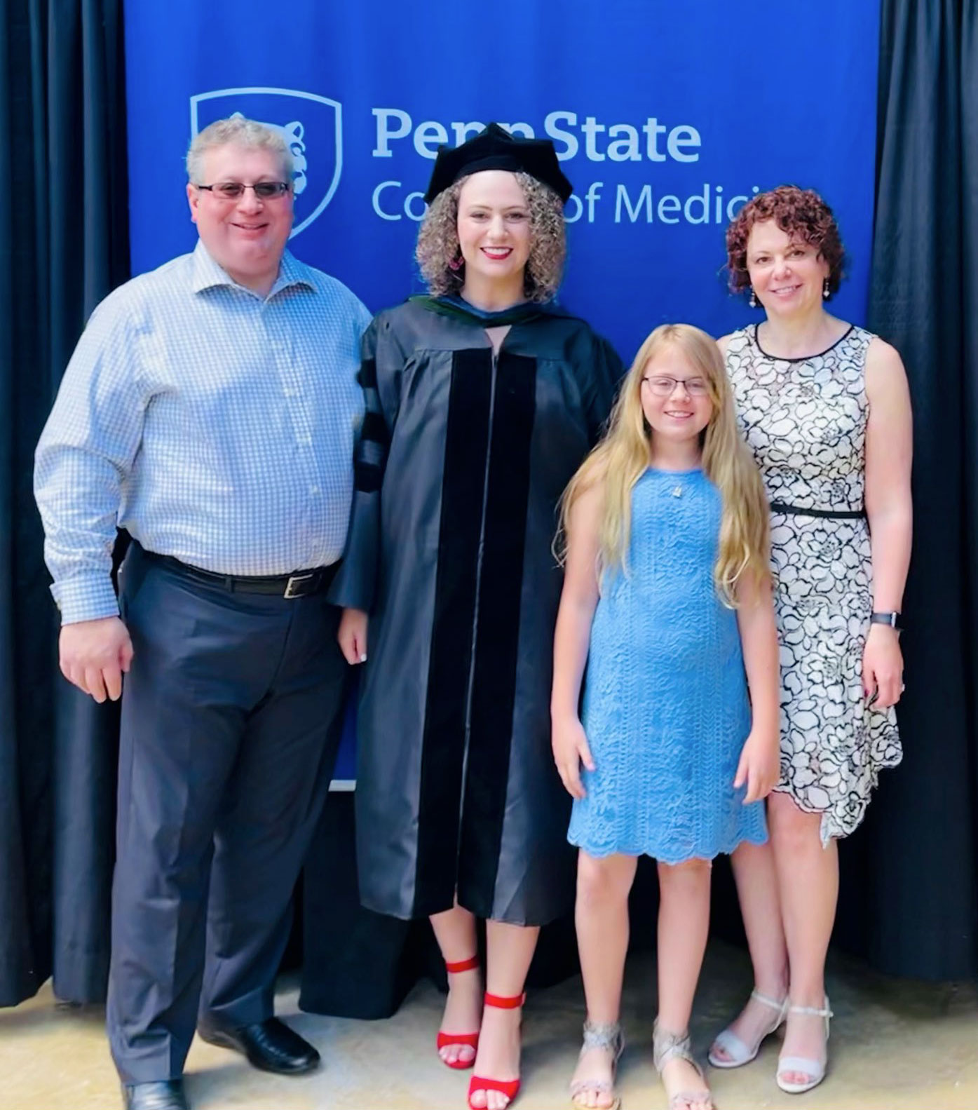 Sarah Erlikh stands with 3 other people in front of a Penn State College of Medicine banner wearing graduation regalia.