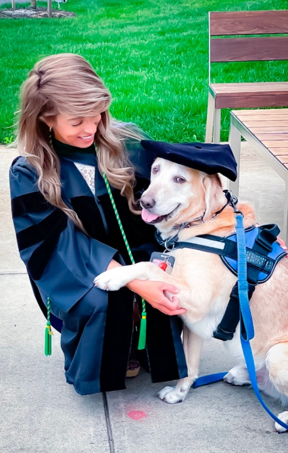 Vanessa Vides kneels next to a dog wearing a service dog harness and her graduation cap. She is wearing a graduation robe.