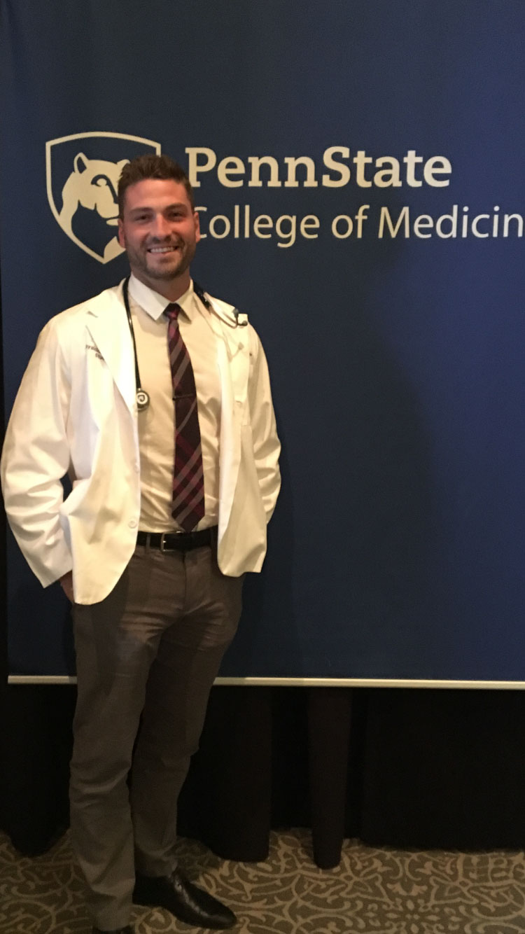 A man wearing a physician assistant professional coat is seen standing in front of a Penn State College of Medicine photo background.
