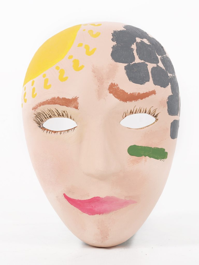 A mask painted like a woman's face, with what appear to be bricks covering the left side of her head and a sun on the right side.