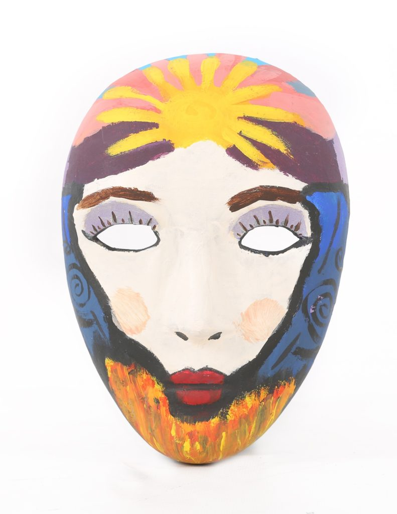A mask depicting a sun over a field of wheat painted on it.