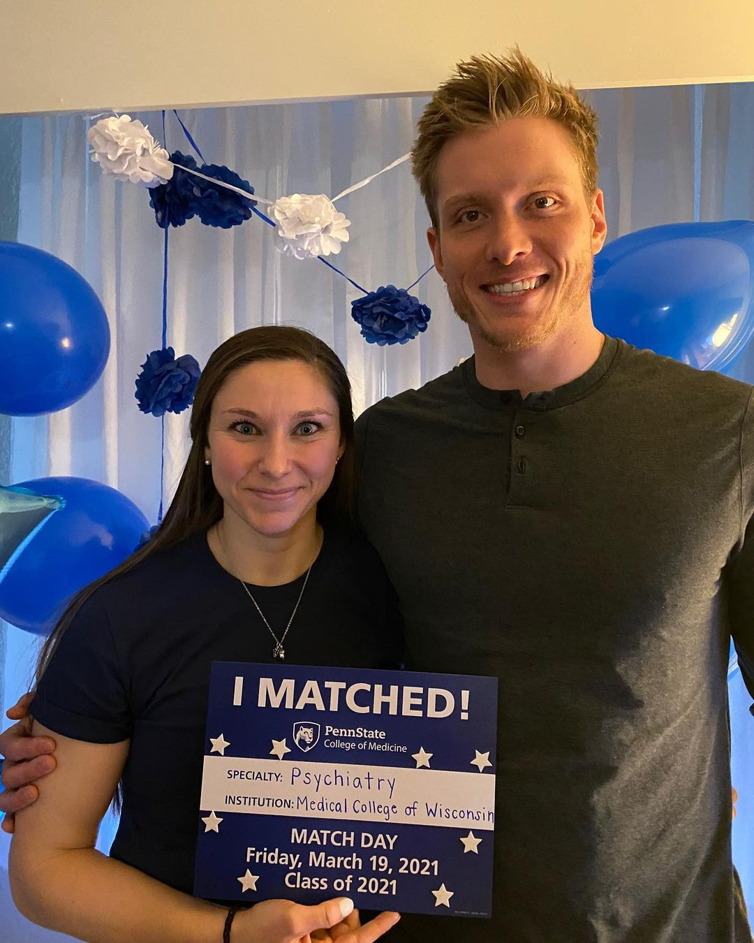 A couple stands indoors holding an I Matched sign for Psychiatry at Medical College of Wisconsin.