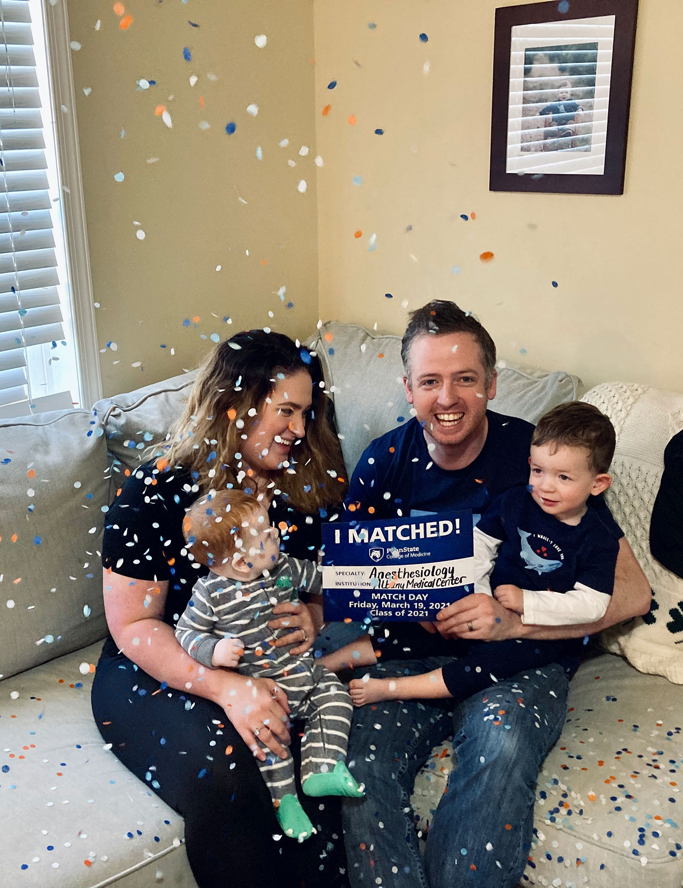 A man, woman and two small children sit on a sofa. Glitter was just tossed over them. The man holds an I Matched sign for Anesthesiology.