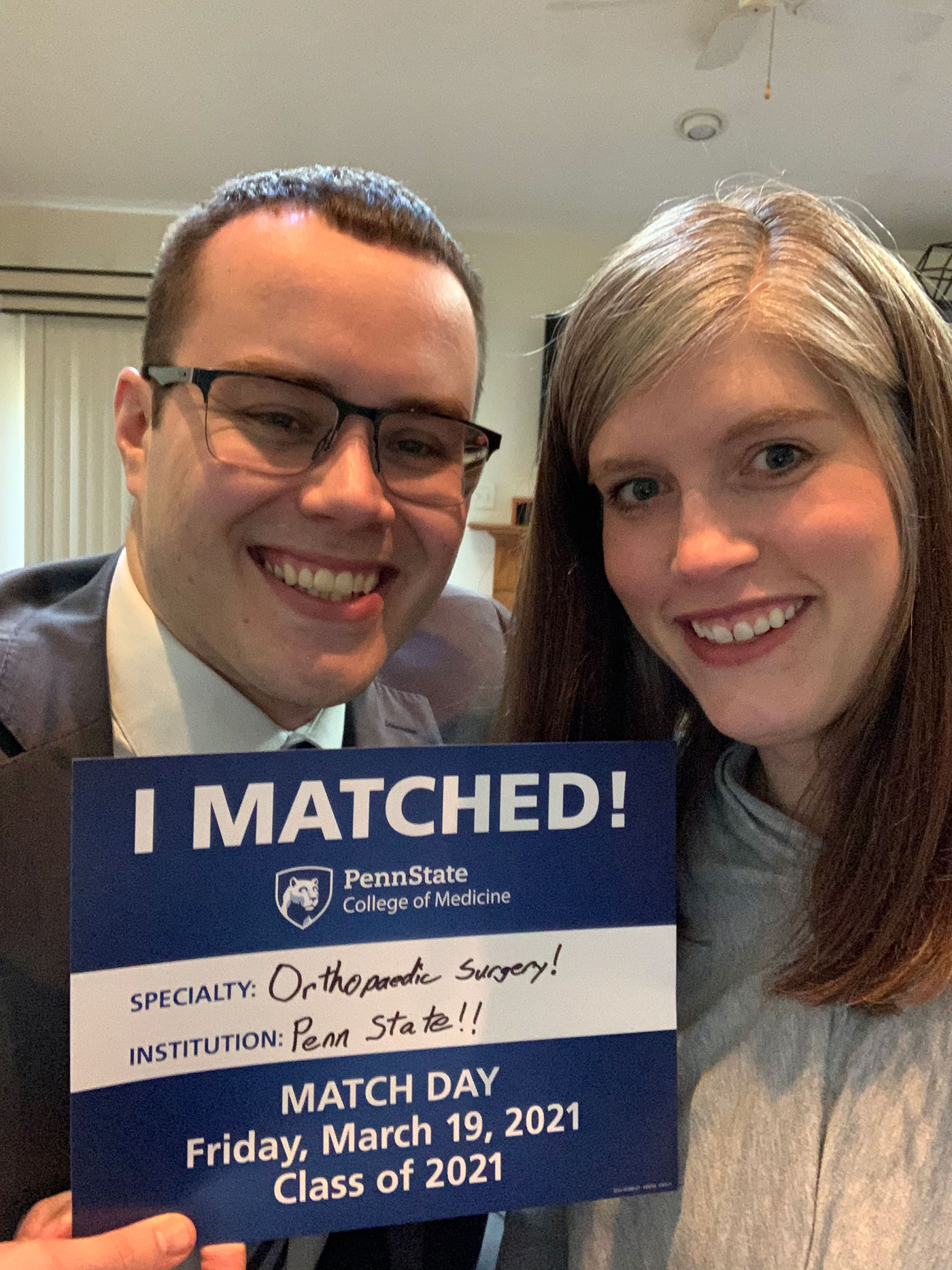 A man and woman hold an I Matched sign for Orthopaedic Surgery at Penn State.