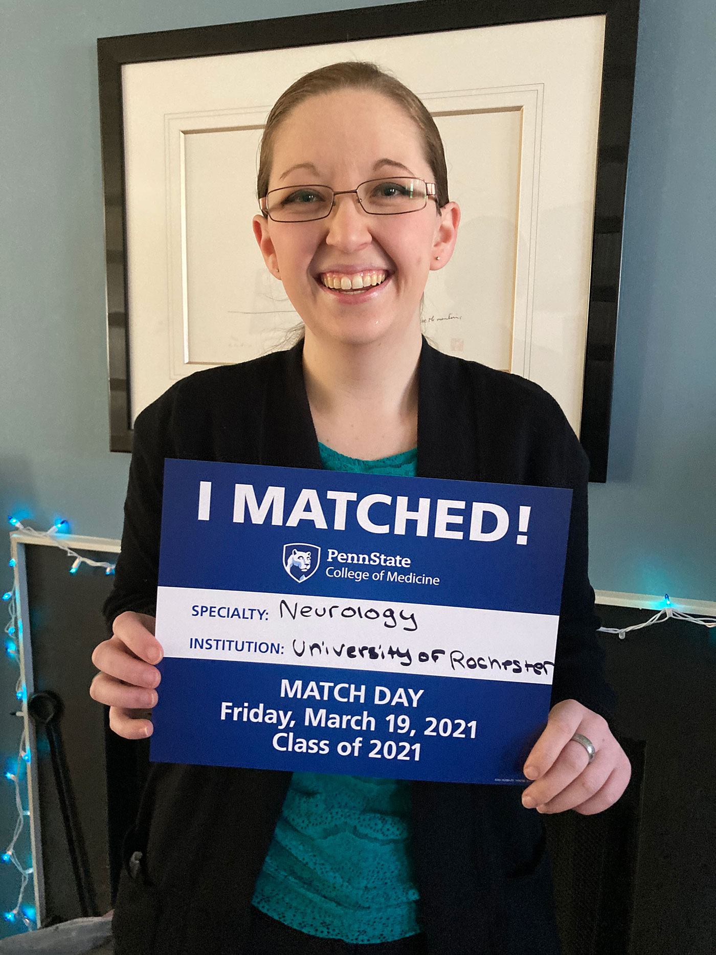 A woman holds an I Matched sign for Neurology at University of Rochester.