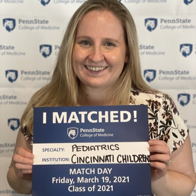A woman holds an I Matched sign for Pediatrics at Cincinnati Children's.