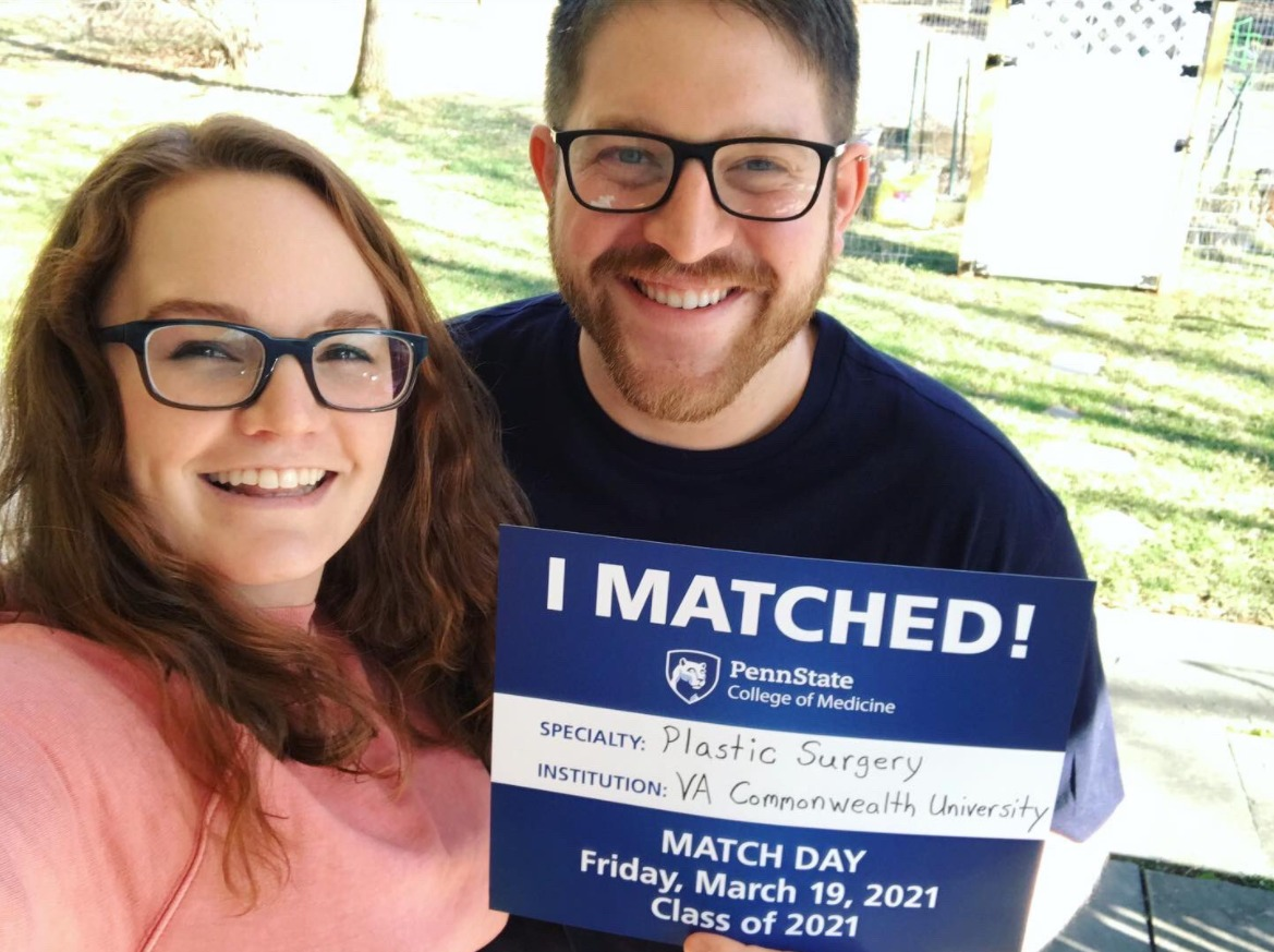 A man and a woman stand together. He is holding an I Matched sign for Plastic Surgery, Virginia Commonwealth University.