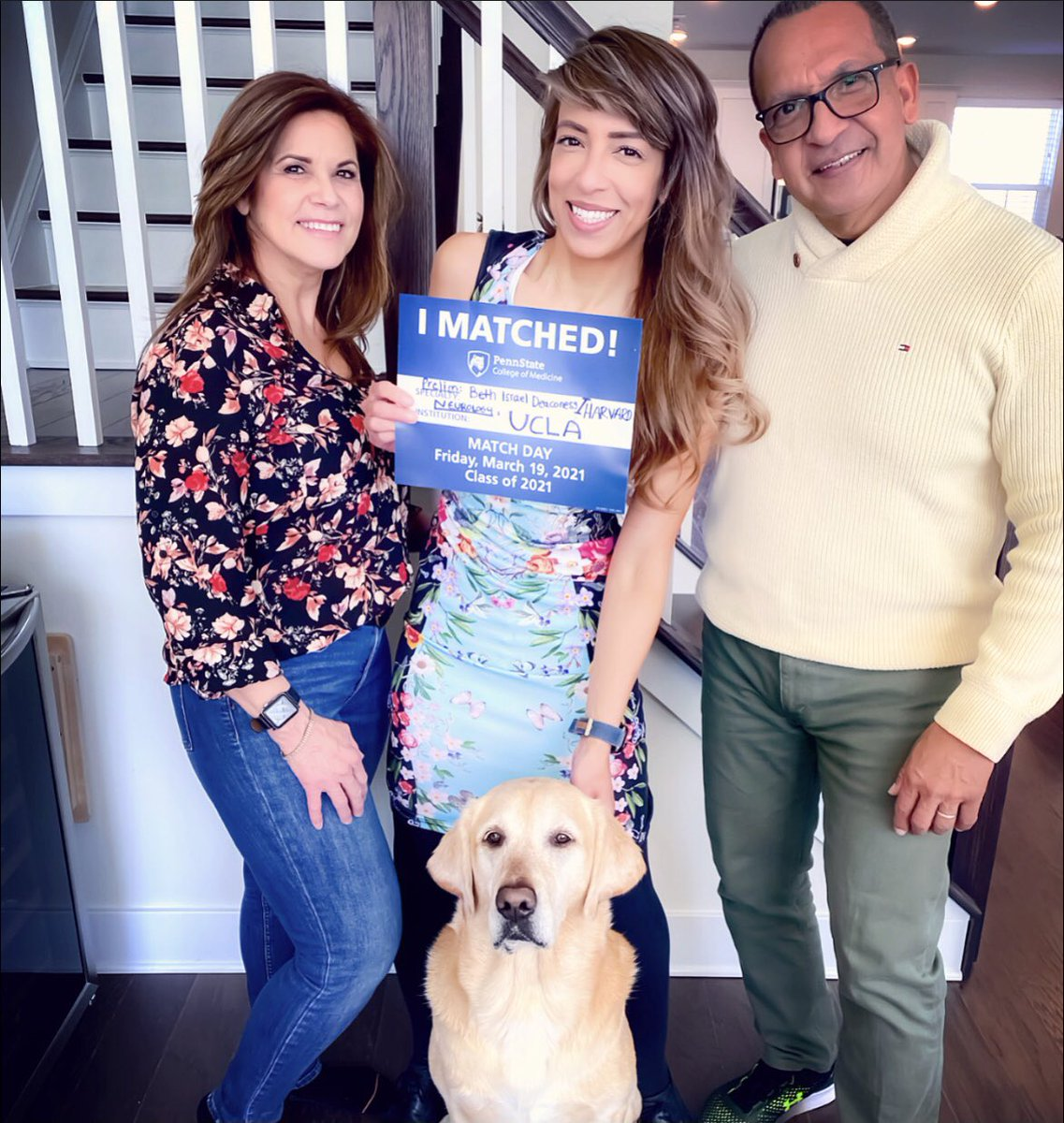 A woman stands between an older couple with a dog in front of her. She holds an I Matched sign for UCLA.