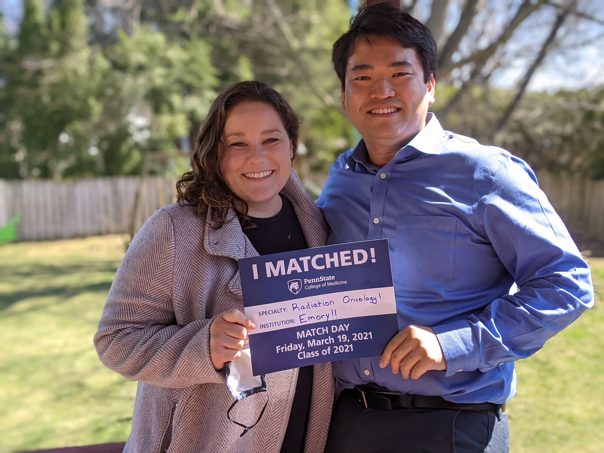 A couple stands outside holding an I Matched sign for Radiation Oncology at Emory.